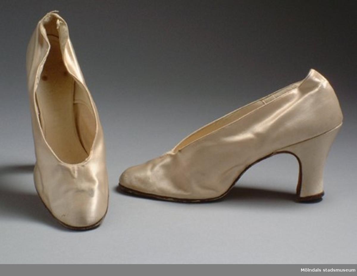 """Naturvit sko med hög klack. Under sulan finns ett """"B"""" stämplat. Användes troligtvis till den första studenthippedressen: invnr. MM03340:1, MM03340:2, MM03340:3.Måtten:Stl. 38, längd 250 mm, bredd 72 mm, höjd 80 mm (klack)."""