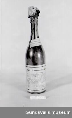 En flaska svart skoltavelfernissa försedd med två pappersetiketter på vilka bruksanvisningen står skriven.