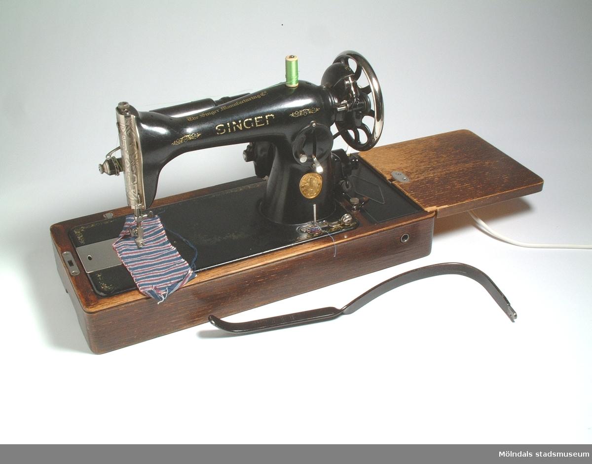 Singer bordssymaskin (MM03853:1) med knähävert och extra skiva. Elektrisk, nyare sladd. Maskinnummer: Y9019177.Knähävert (MM03853:2), längd 510 mm.Extra skiva (MM03853:3), 212 mm x 211 mm.2 spolar (MM03853:4), diameter 20 mm.När givaren var två och ett halvt år gammal, 1919, flyttade familjen från Borås till Mölndal. Pappan, Oskar Andersson, arbetade till en början på Papyrus och senare på försäkringsbolaget Trygg.Gamla torget var då centrum i Mölndal och hade torghandel på lördagarna, och givaren fick följa med sin mamma, Hulda Andersson, dit och handla.Det roligaste mamman visste var att få sitta vid symaskinen och sy och att rita modeller. En dag fick hon en idé, att stå på torget och sälja det hon sytt. Försäljningen gick bra, och efter en tid hyrde man en lokal på Kvarnbygatan 2 eller 3 och startade där Borås Stuvaffär. Verksamheten utökade 1923 med ytterligare en affär och en syateljé i Broslätt, och då inköpte man den Singer bordssymaskin som skänkts till Mölndals museum. Konfektionssömnad hade inte kommit igång på 1920-talet, och man sydde t ex. damunderkläder, nattlinnen, herrnattskjortor, förkläden och en del barnkläder.Givaren tog över affären i Broslätt 1948 och innehade den fram till 1962.Läs även givaren Margit Svennings minnesanteckningar i Mölndals museums arkiv.