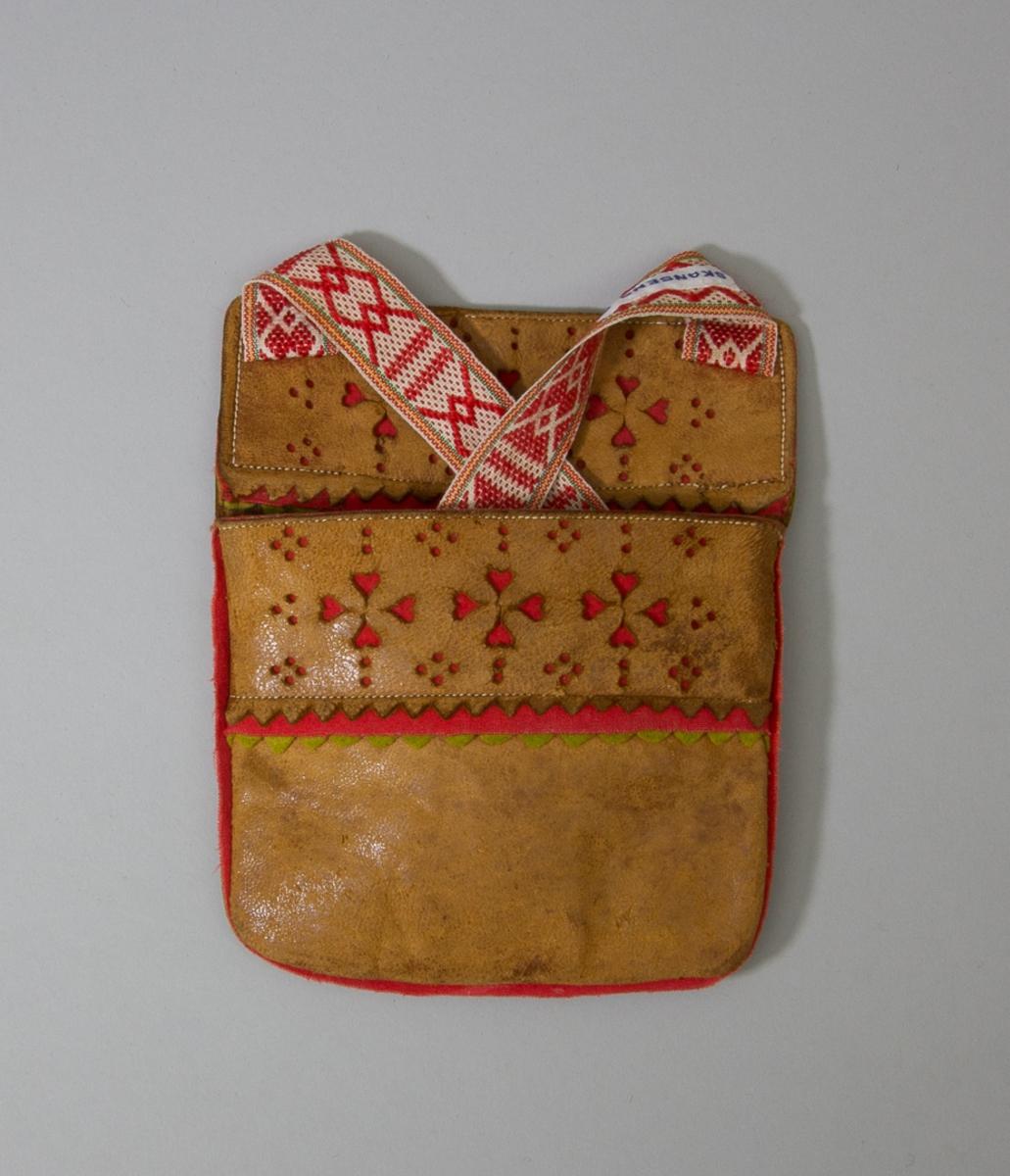 Kjolsäck till dräkt för kvinna från Mora socken, Dalarna. Modell med avskuret framstycke. Tillverkad helt av brunt kalvskinn. På framstycket och på överstycket en remsa av kalvskinn med stansade hål fastsydd på maskin. Under skinnremsan ligger en remsa rött kläde, som lyser igenom hålen. I nederkanten dessutom en remsa grönt kläde, klippt i uddar. En remsa rött och en remsa grönt kläde inlagd i sido- och bottensömmen. Axel- eller midjeband vävt med plockat mönster i rött ullgarn på vit botten, möjligen maskinvävt.