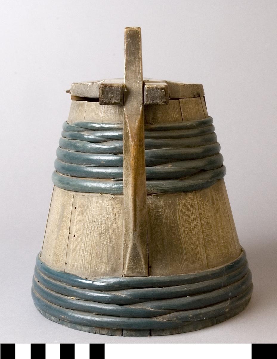 Kanna av laggat trä med pip, lock och handtag. Runt om kannan finns band av vidjor. Vidjorna är målade med blått. Locket är dekorerat med blomstermåleri. Locket är gängat med tapp i handtaget.