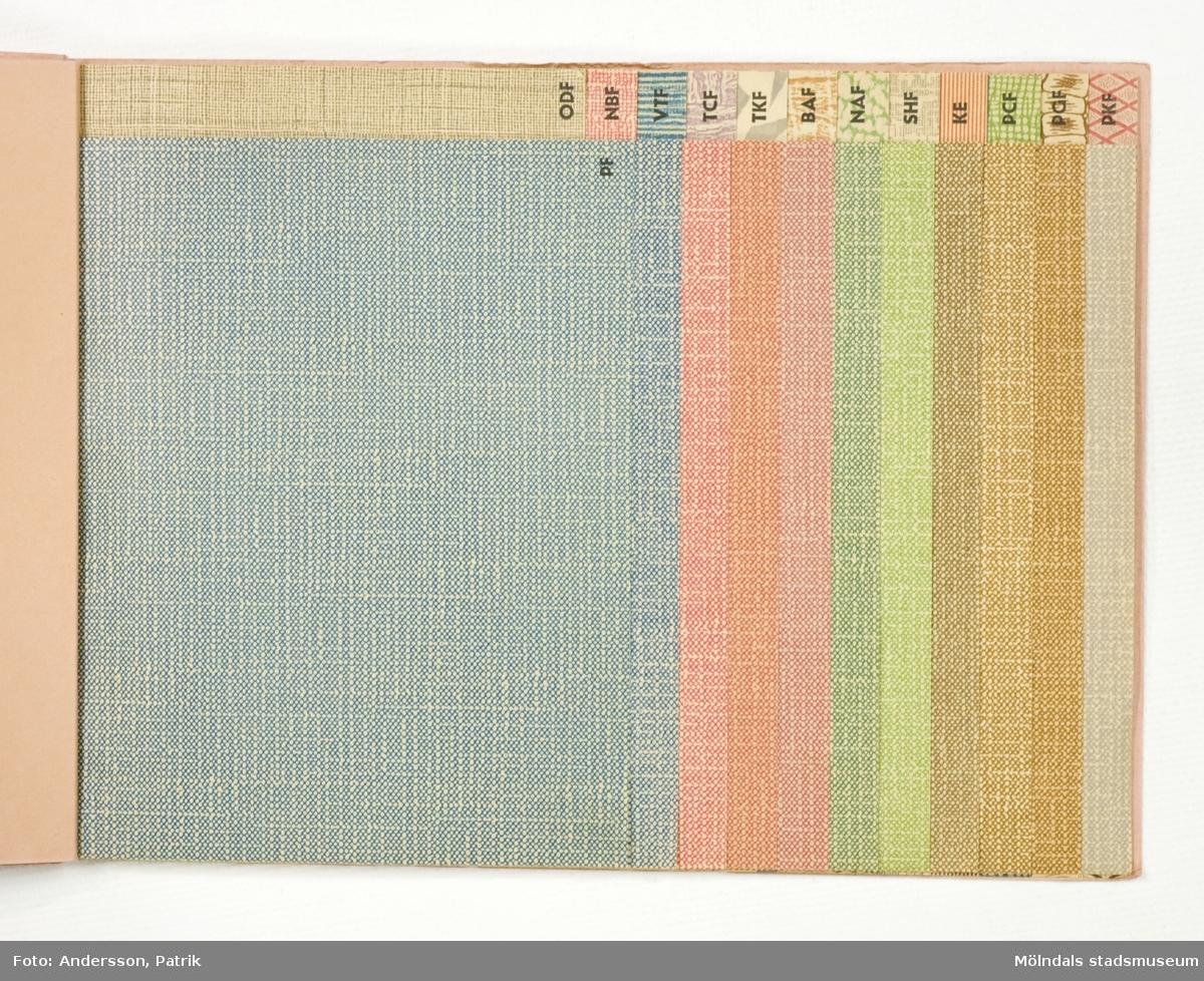 """Provbok 69A. Häfte med prover, """"Colour-Embossed Fancy Papers"""". Papyrus logotyp med sfinx på fundament och tillverkarnamn. Produktinformation. Provark i olika storlekar, ordnade lättöverskådligt. Litteratur: Papyrus 1895-1945, Minnesskrifter, Esseltes Göteborgsindustrier AB, Göteborg 1945."""