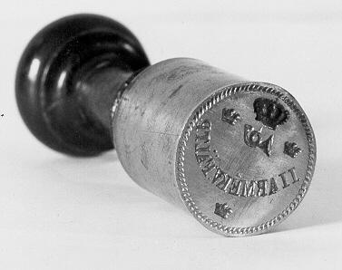 """Sigillstamp av stål, med sprucket, svarvat, svart träskaft.Sigillet runt med en kunglig krona överst. I kronan hänger ettposthorn. På sidorna om posthornet och under texten finns Tre Kronor.I mitten, i en båge står texten """"II ARM@KV. FÄLTP."""" i antikvastil.Sigilltypen användes troligen från 1860 - talet fram till 1910 -talet."""