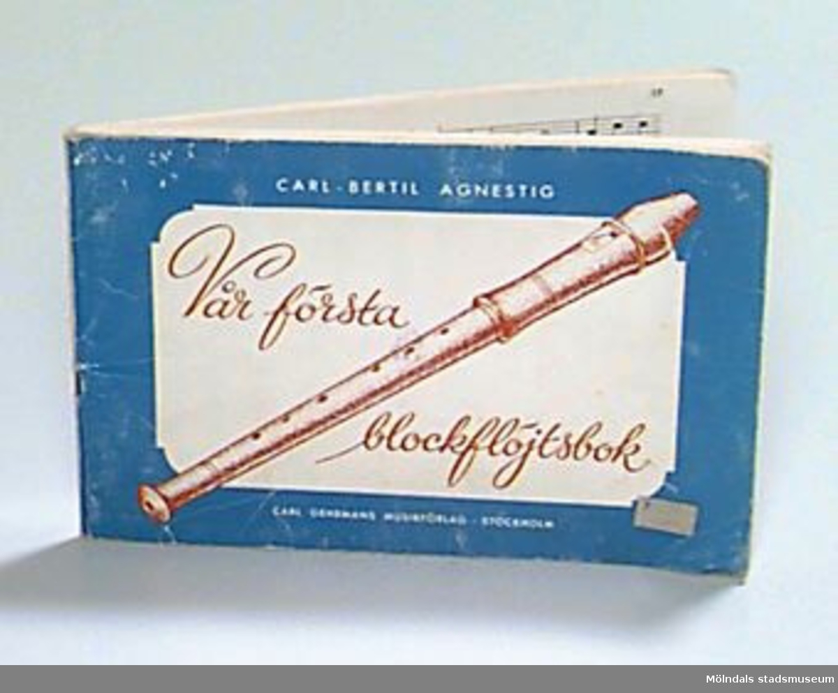 """Blå och vit bok med text i vitt och rostrött, samt en teckning av en blockflöjt i rostrött.             Prislapp på framsidan.På sidan tre en stämpel: """"Mölndals museum"""" , samt skrivet med blyerts: """"Xfa"""", en ämneskod från museets bibliotek, där boken tidigare var placerad. På näst sista sidan är siffror skrivna med blyerts, och på bakre pärmens insida är skrivet med blyerts: """"G. Sven-Erik Johansson 3/10 -90""""."""