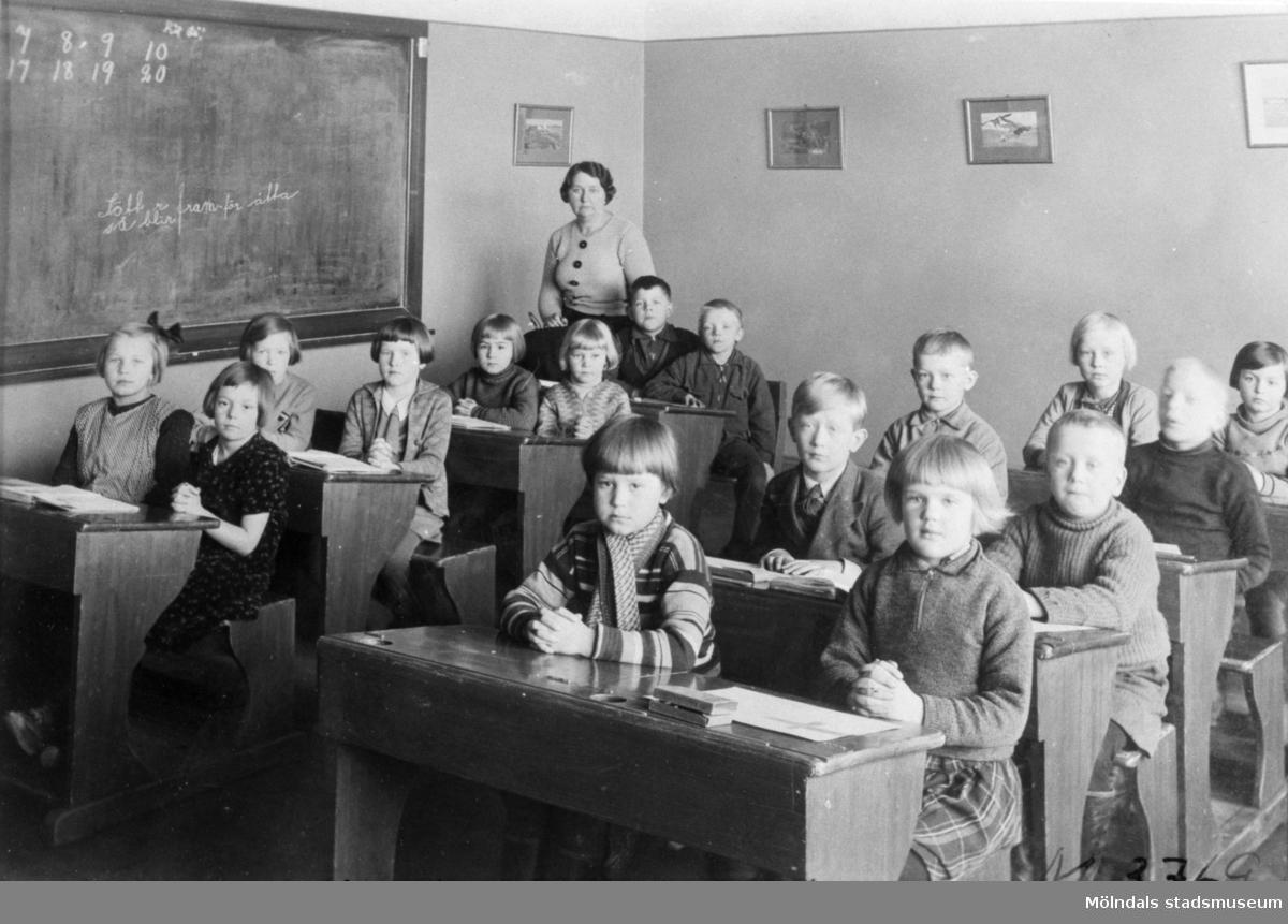 Flickor och pojkar sittandes i skolbänkar på Krokslättsskolan 1924. Läraren Rosa Hagström med elever. Andra från vänster, bakre raden sitter Iréne Magnusson. Anna-Greta sitter bredvid Iréne. Viola i zickzackmönstrad kofta sitter nedanför lärarinnan.  Ing-Britt? Evan och Gullvi främst i bild.