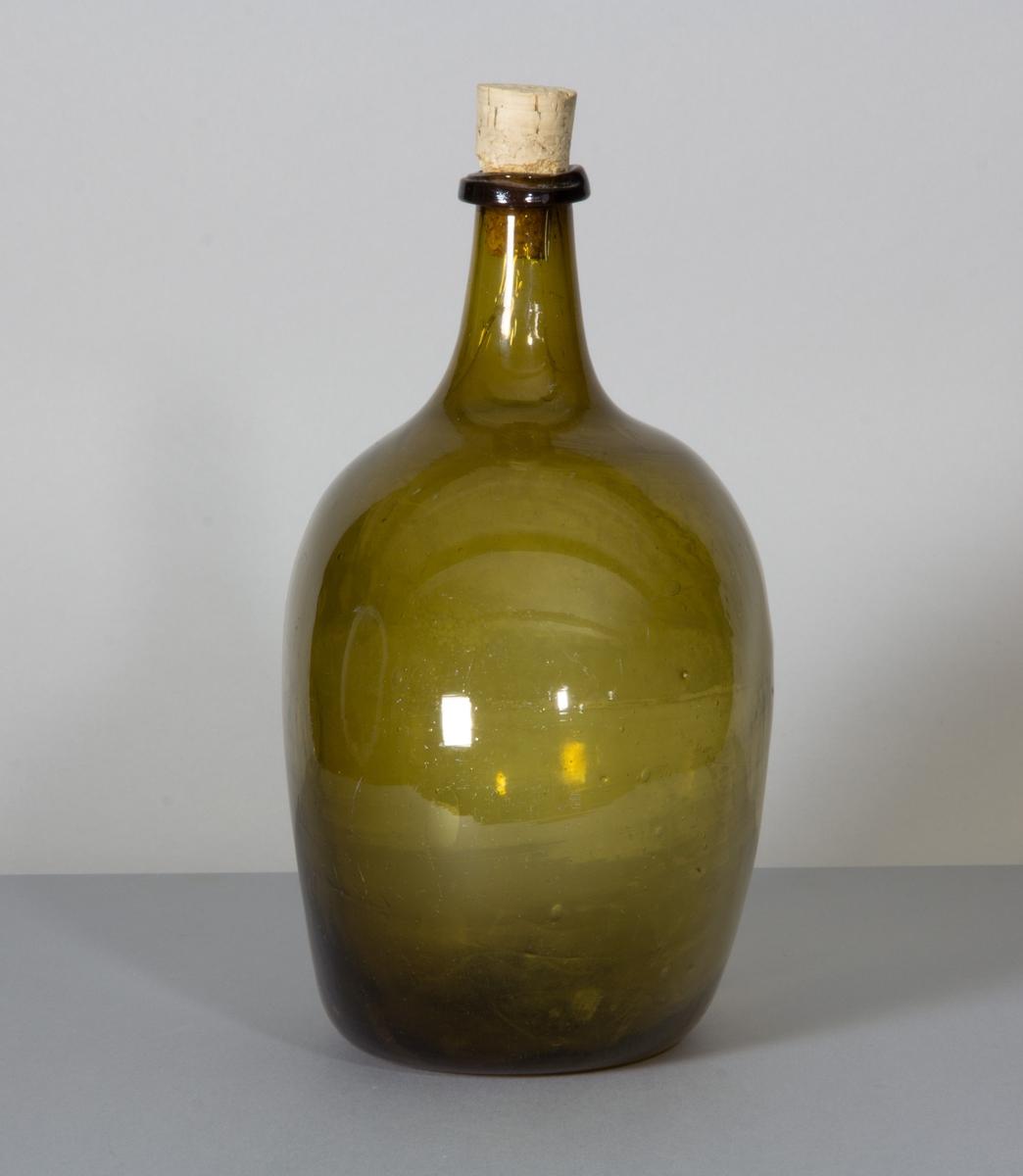 Flaska i glas, brungrön till färgen. Rundade sidor, hals med halsring och platt botten.