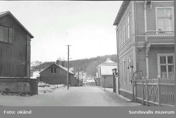 Holmgatan samt skylt med Sundsvalls bryggeri. Till vänster Östbergska gården och till höger Lindgrenska arbetsinrättningen (senare Holmgården).