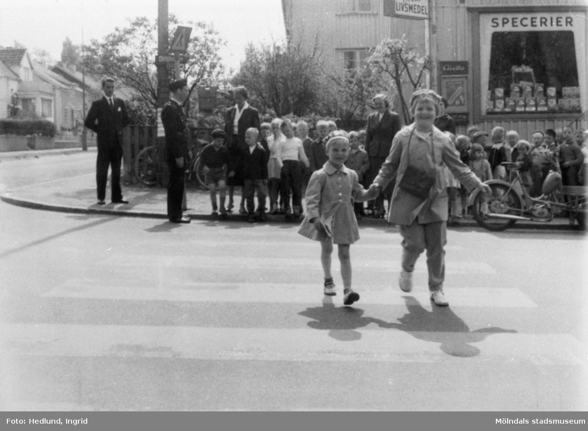 Barn som går över gatan på ett övergångsställe.
