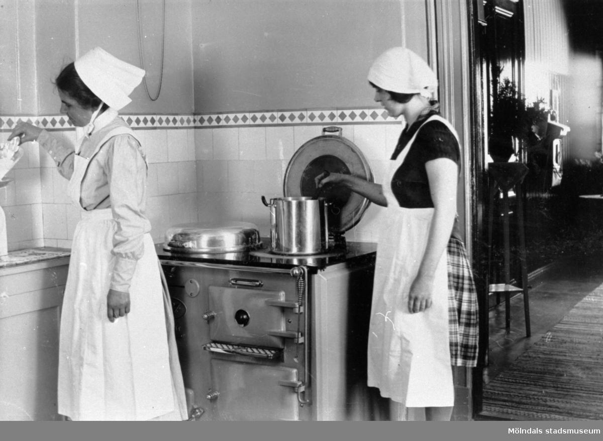 Skolköksinteriör på Trädgårdsskolan, 1900-tal. Två kvinnor lagar mat. Vedspis i köket.Se även MMF1992:0033