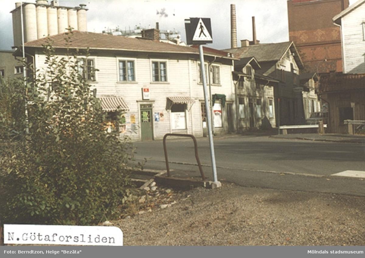"""Nedre Götaforsliden tagen från platsen där man förr sålde fisk, """"feskeflöten"""". Tobaksaffär och Johanssons järnaffär i bakgrunden. 1970-talet"""