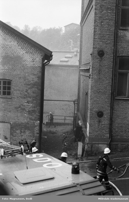 Soab-branden i Stora Götafors den 4 juni 1986. Brandmän och brandbil står på Götaforsliden utanför Nymans kvarn till vänster och Stora Götafors till höger.