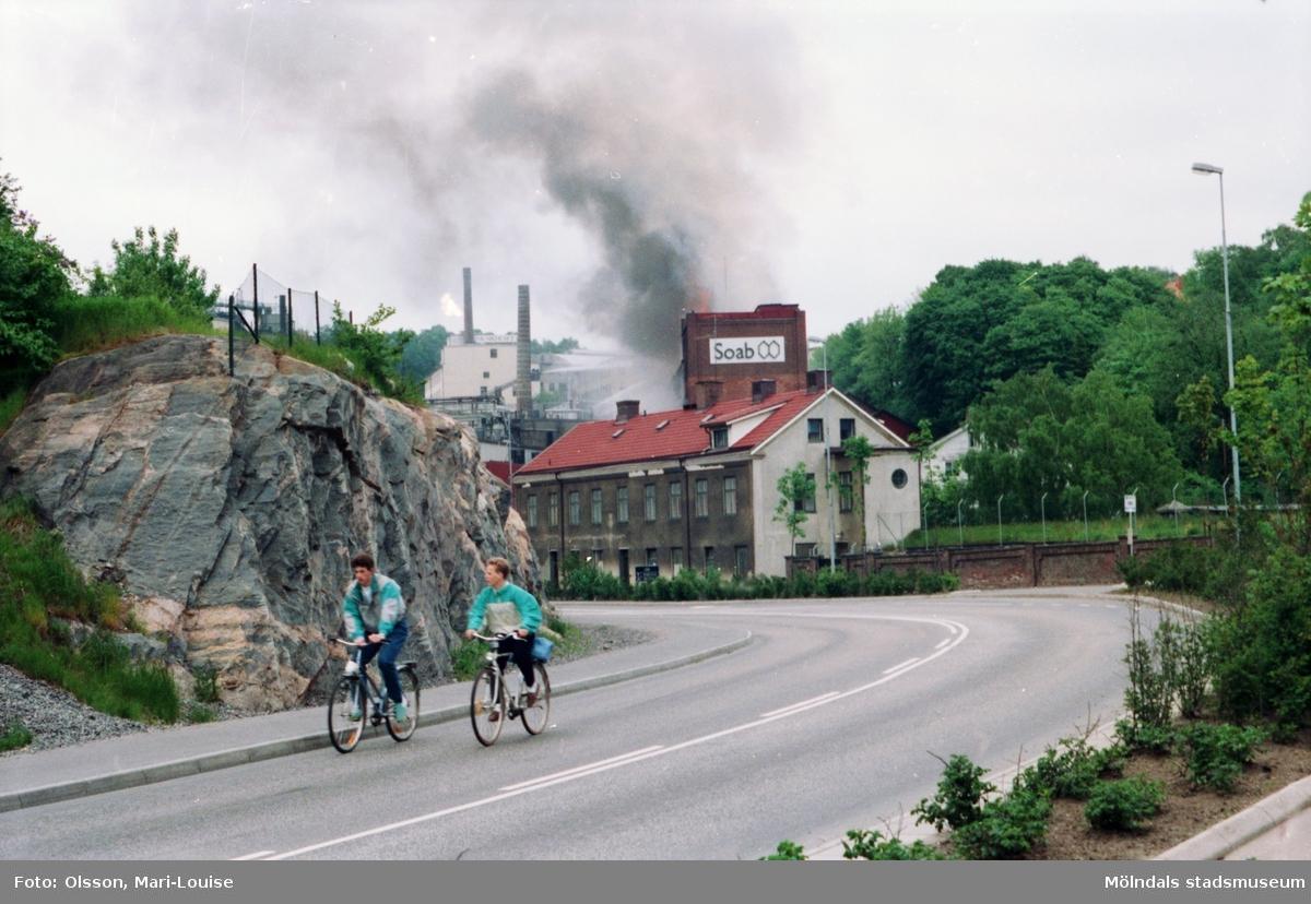 Soab-branden i Stora Götafors den 4 juni 1986. Två personer som cyklar utanför Papyrus mur.