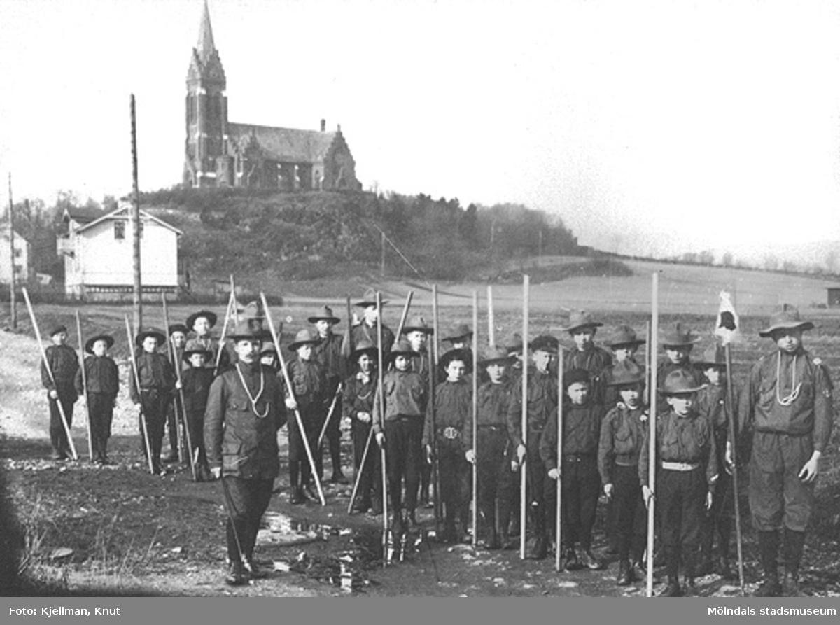 En scoutkår som är utrustad med patrullflagga och långa käppar. Fässbergs kyrka syns i bakgrunden. Mölndalsbro tidigt 1900-tal. Urklipp från en almanacka.