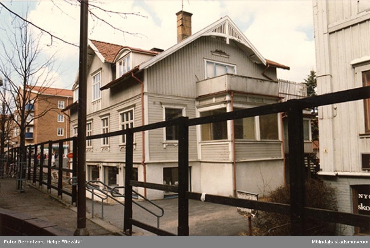 """En glasbutik och presentaffär fanns i bottenvåningen fram till rivningen. Presentaffären hette """"Allehanda"""", och huset har genom åren ägts bl.a 2x familljen Kristoffersson (möbelaffären vid Kvarnbygatan). Dessförinnan fanns i fastighetens första våning doktor Sandströms mottagning. Harald Sandström var även skolläkare i Centralskolan/Kvarnbyskolan, och förflyttade sig under en tid med en Jowett Javelin, en engelsk bil. Märket är sedan 1950-talet saligen avsomnat. Huset hette Westanå. Frölundagatan 6 eller Mölndalsbro 52. Kortet taget maj 1986."""