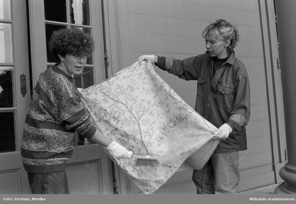 Antikvarisk storstädning på Gunnebo slott 1992. Ulla Hasselqvist och en annan kvinna borstar av ett tygstycke.