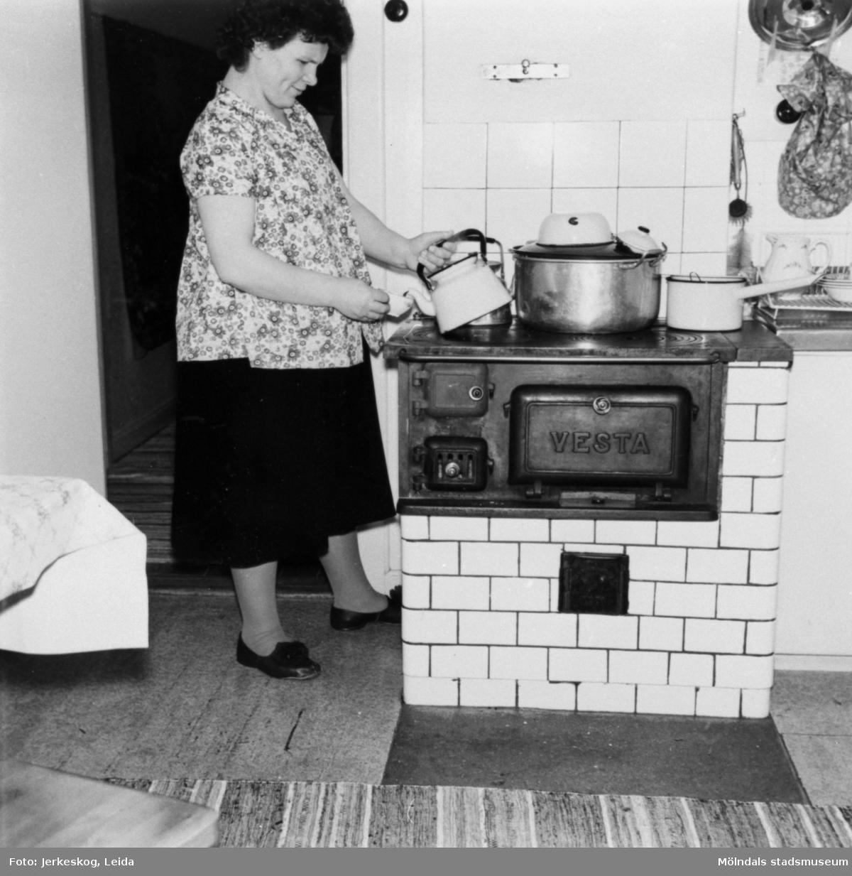 """Lisa Honkavaara kokar kaffe vid """"Libergs"""", intill spinneriet, vintern 1957."""