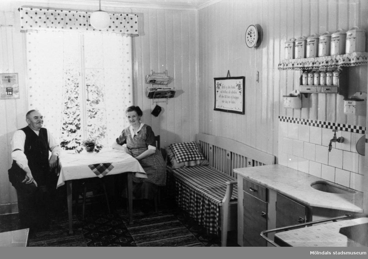 Arbetarbostad som troligtvis tillhör Krokslätts fabriker. Köket med de boende vid köksbordet.