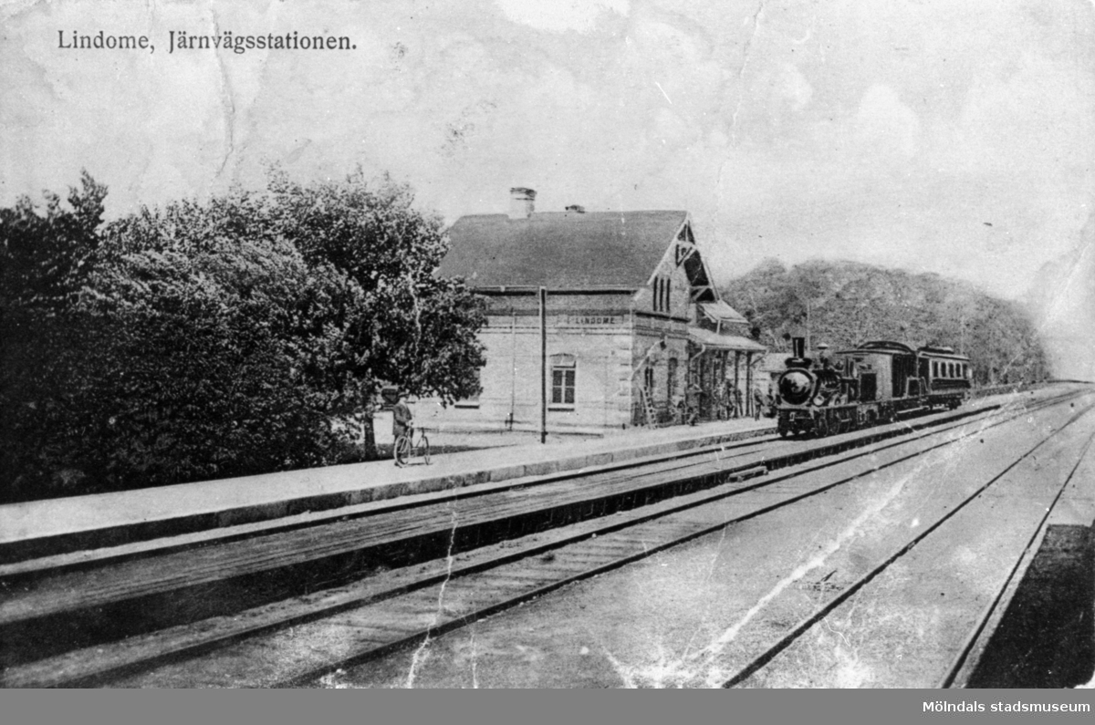 Ånglok med vagn vid gamla Lindomes järnvägsstation, i slutet av 1800-talet.  Den gamla järnvägsstationen i Lindome låg på västra sidan om järnvägen, ungefär där det idag ligger en pressbyråkiosk. Den revs 1921 i samband med att järnvägen byggdes om. Tidigare gick spåret på västra sidan om Sagsjön, där var det sankt och bottenlöst, så att ett lok med förare och allt gick ner och sjönk. Loket med förare ligger kvar i djupet än idag. Efter denna händelse byggdes järnvägen rakt över Sagsjön, fyllnadssten bröt man där Makadambolaget ligger idag och det är därför Makadambolaget har hamnat där. Det byggdes också en ny järnvägsstation samma år, 1921.