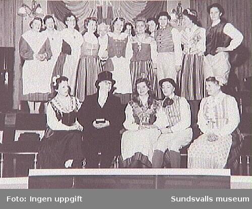 Medlemmar i Sundsvalls Martha-förening framför teaterspel i Stadshuset, 1959. Sittande i mitten Alma Carlsson (som präst), Aina Nilsson, Elna Andersson.