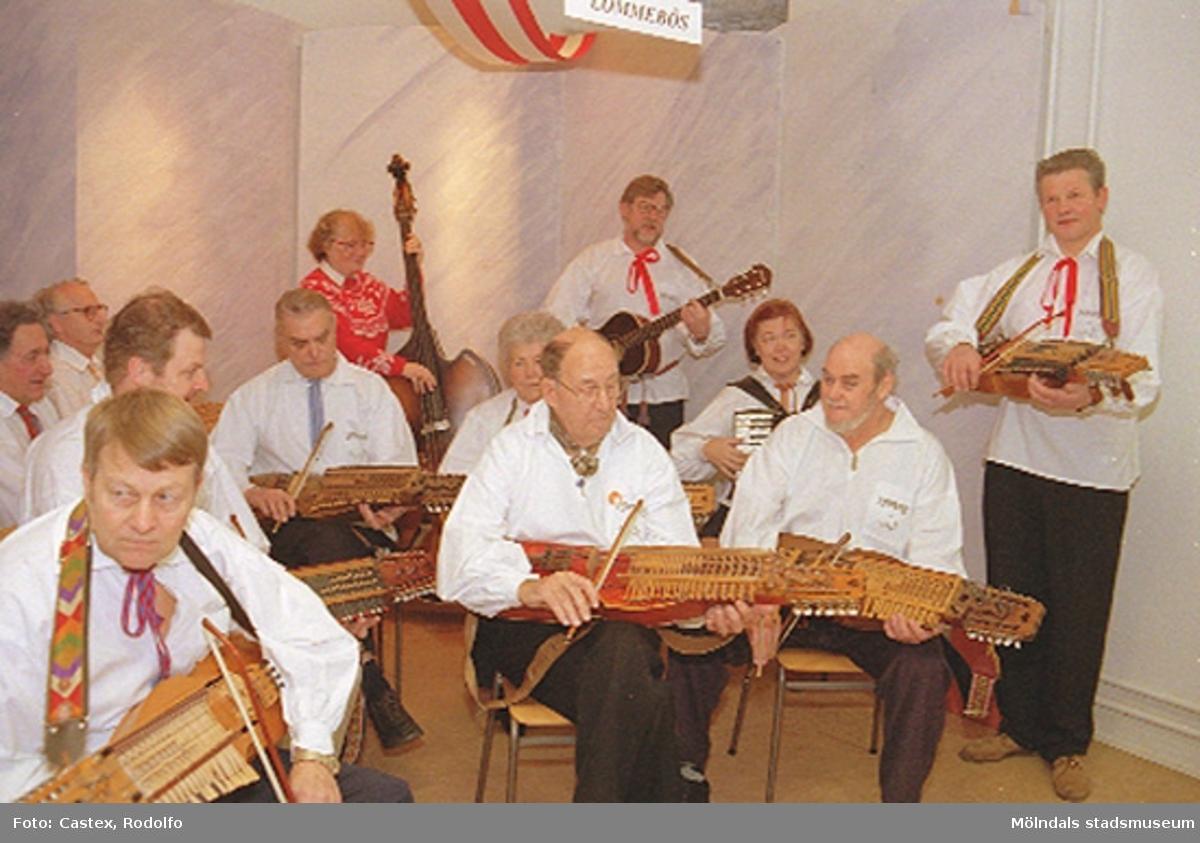"""Julmarknad på Mölndals museum 1994-12-03. Hällesåkers Spelmanslag """"Lômmebôs"""" (Lömmebös) spelade nyckelharpa. Till höger står museets tekniker Sven-Åke Svensson."""