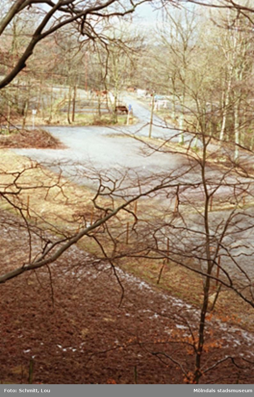 En parkeringsplats. Till höger syns betande hästar och skymten en röd lada. Gunnebo slott ligger i närheten.