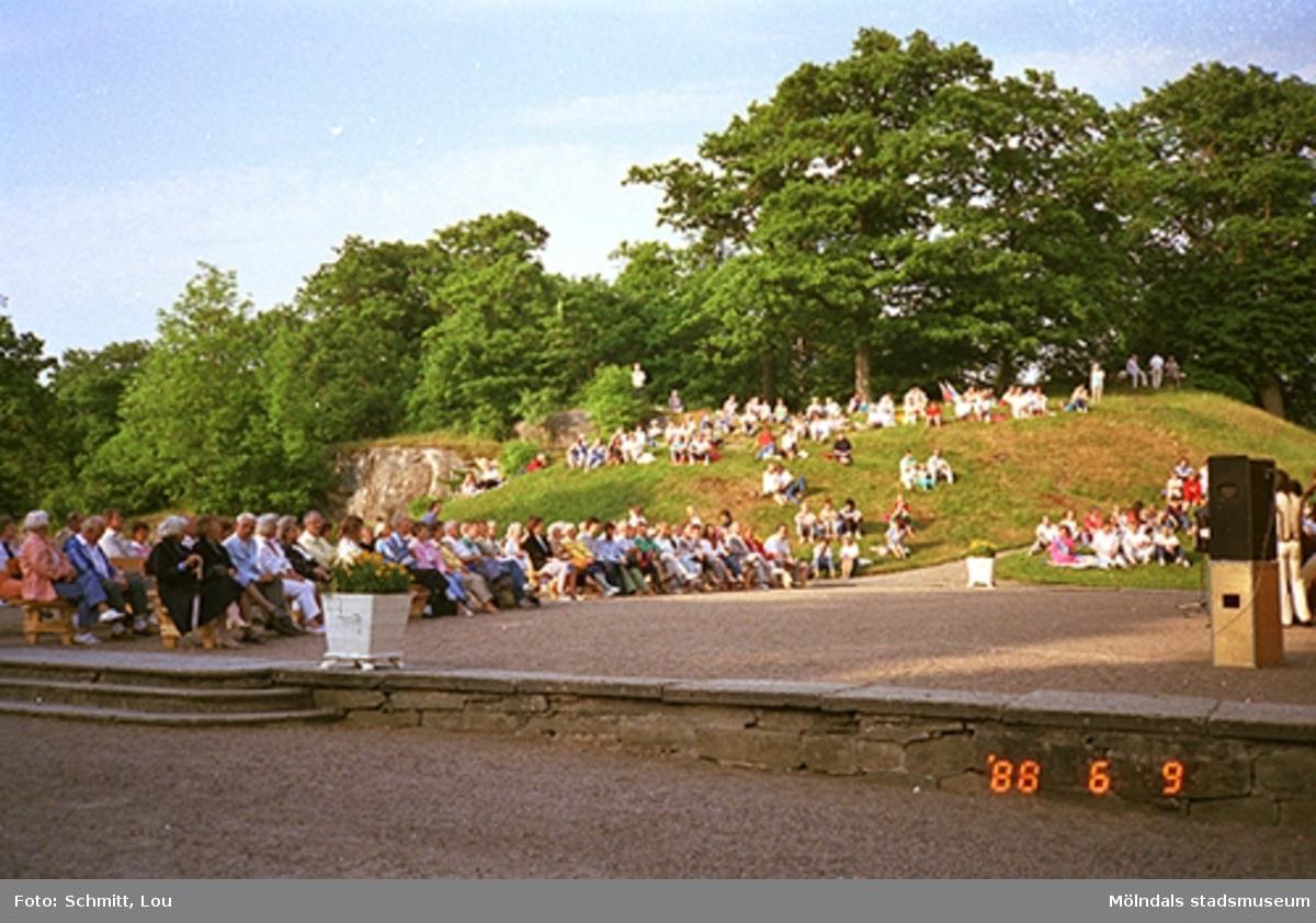 Musikunderhållning av en orkester vid Gunnebo slotts framsida. Människor sitter i gräset och på bänkar.