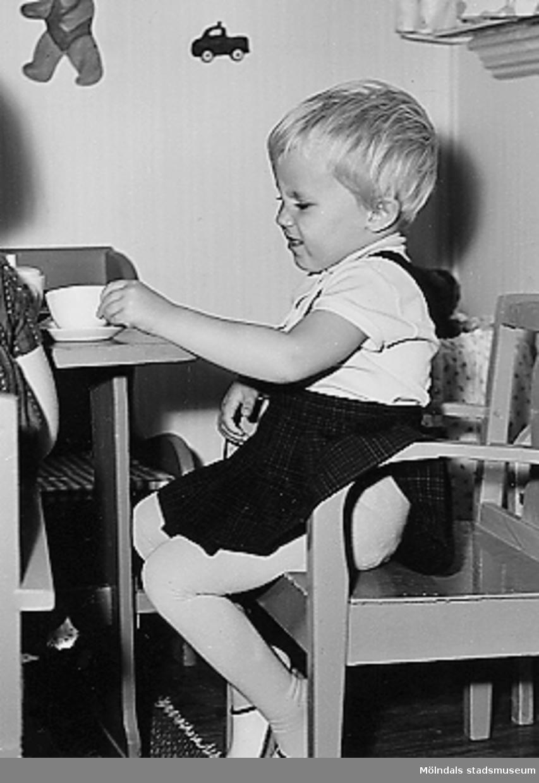 En flicka sitter vid ett bord och har ett set med kopp och fat framför sig. Holtermanska daghemmet 1953.