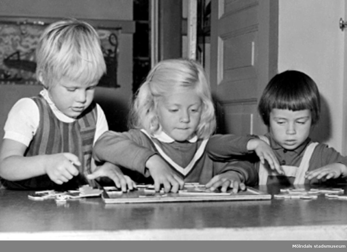 Tre flickor som hjälps åt med ett pussel. Holtermanska daghemmet 1953.
