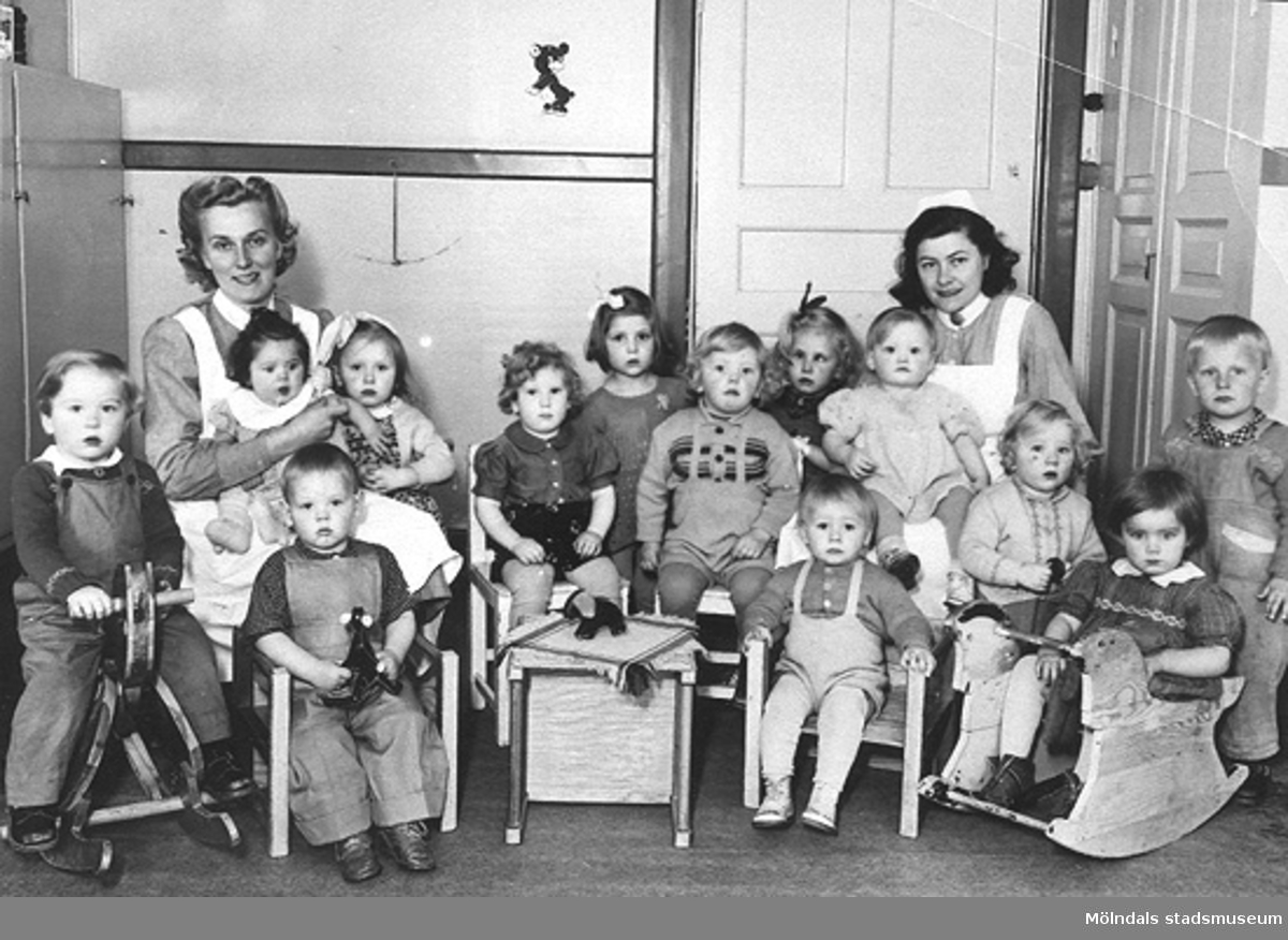 Grupporträtt på fröknar tillsammans med en grupp barn. Holtermanska daghemmet, 1940-tal.