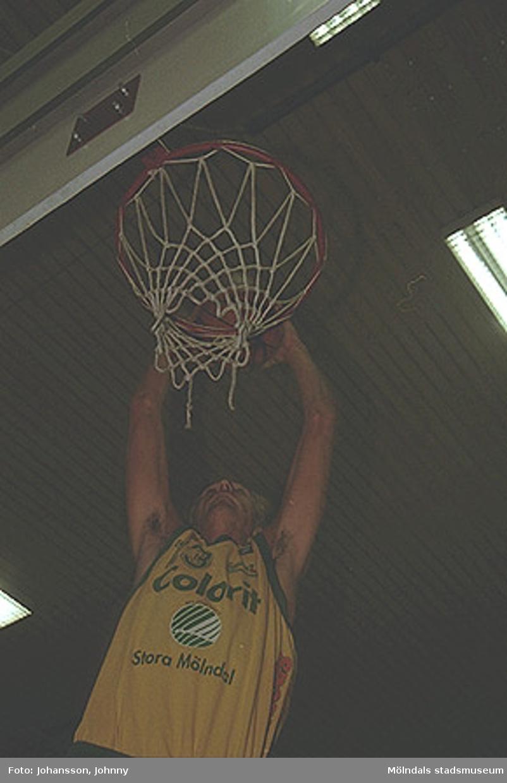 Basketspelare från Kvarnby basket som lägger mål. Han har reklamtryck Colorit på sin tröja. Kvarnby basket var på denna tid sponsrade av Stora Mölndal (f.d Papyrus).
