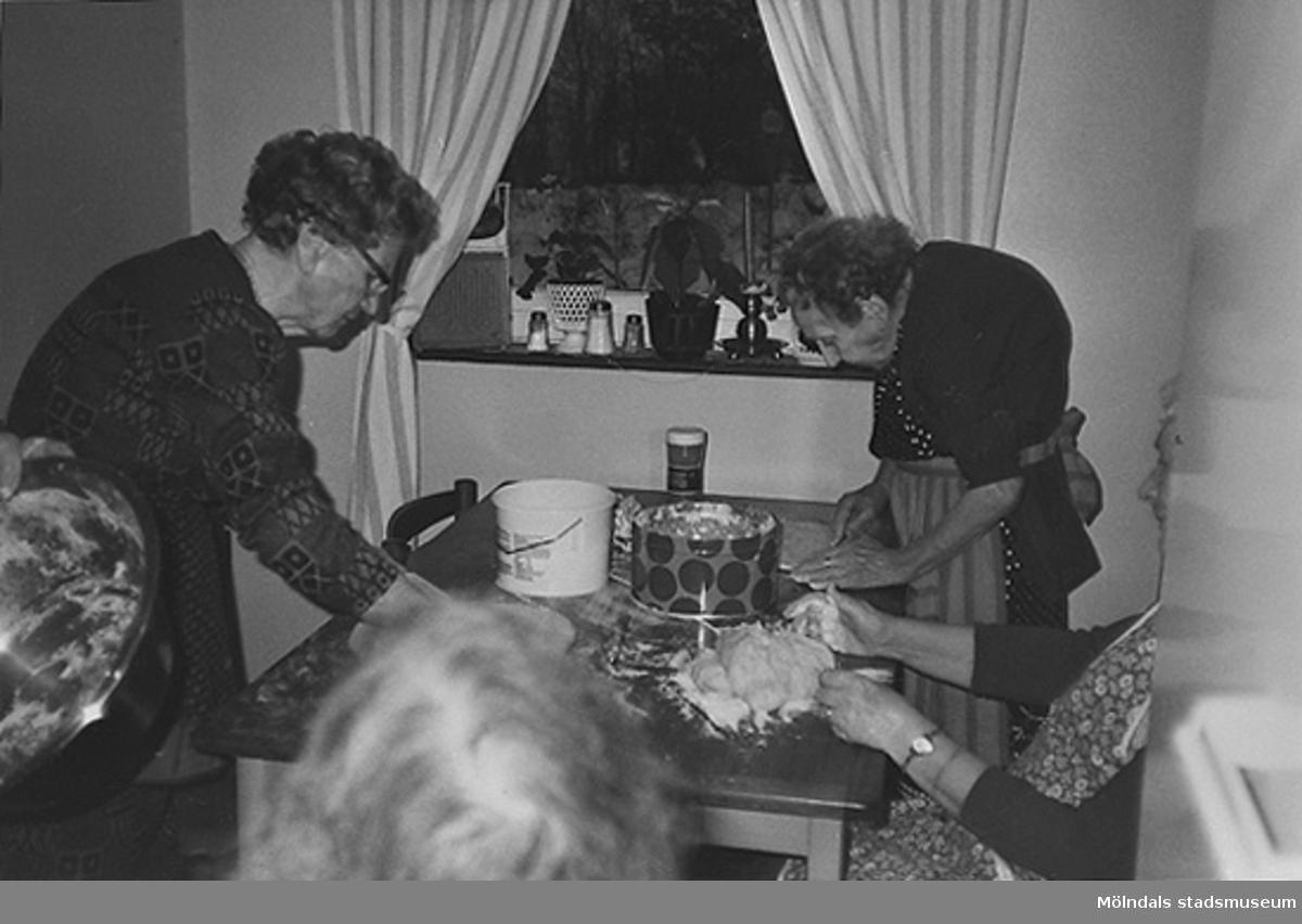Två kvinnor skär upp kaffebröd vid ett köksbord på ålderdomshemmet. Okänt årtal.