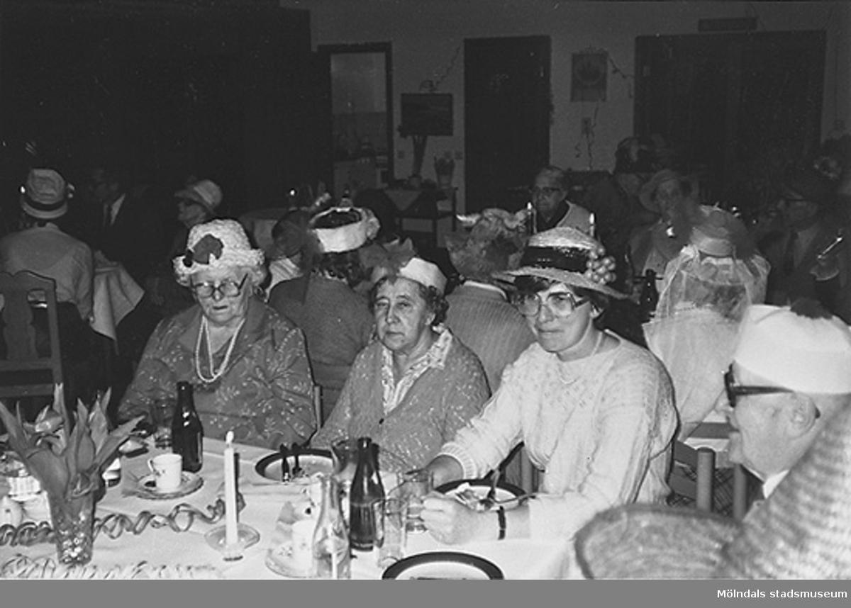 Personer iklädda hattar sitter vid långbord. De har fikat klart. Okänt årtal.