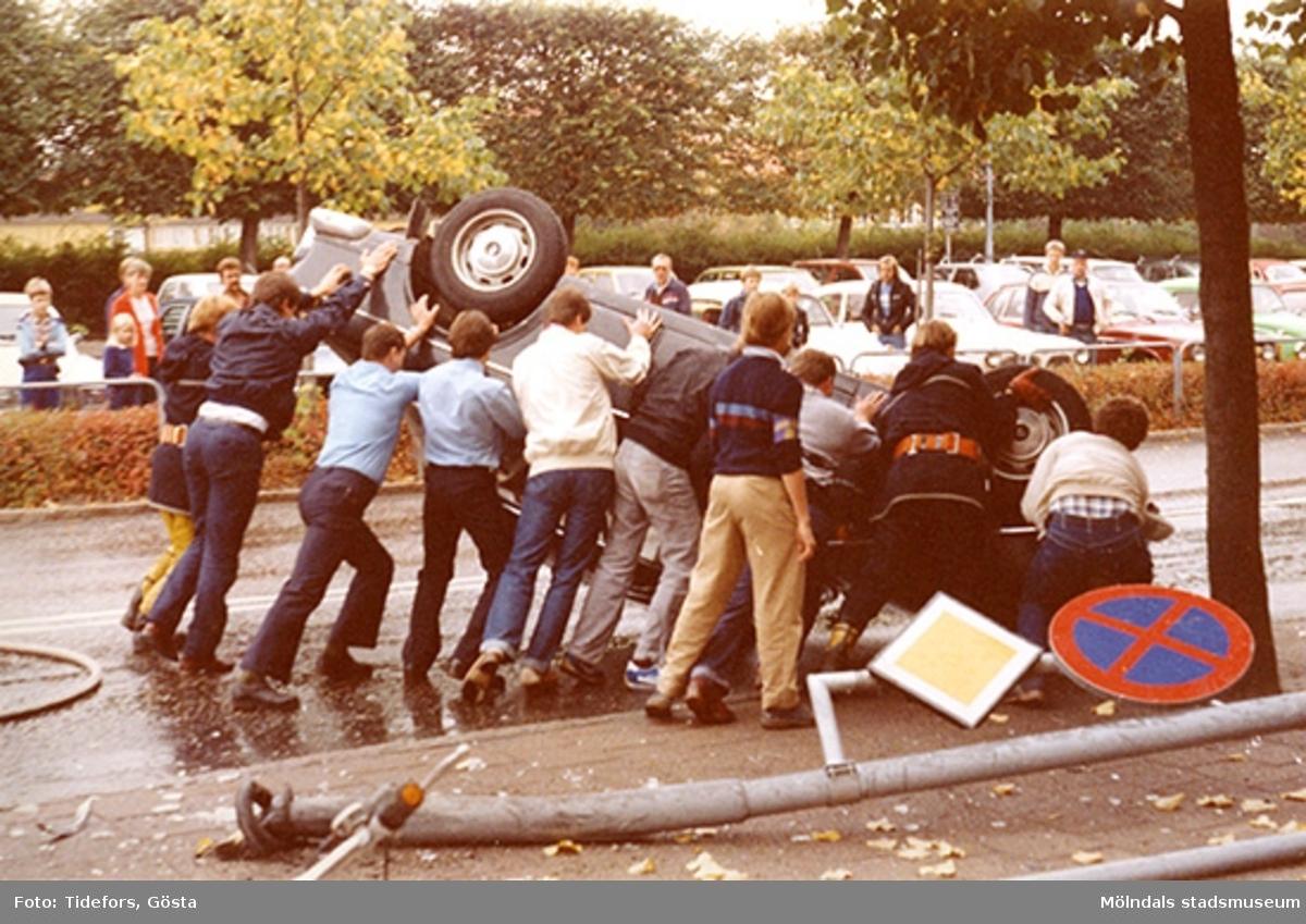 Människor hjälps åt att vända på den upp-och-ner-vända bilen, 1970-tal.