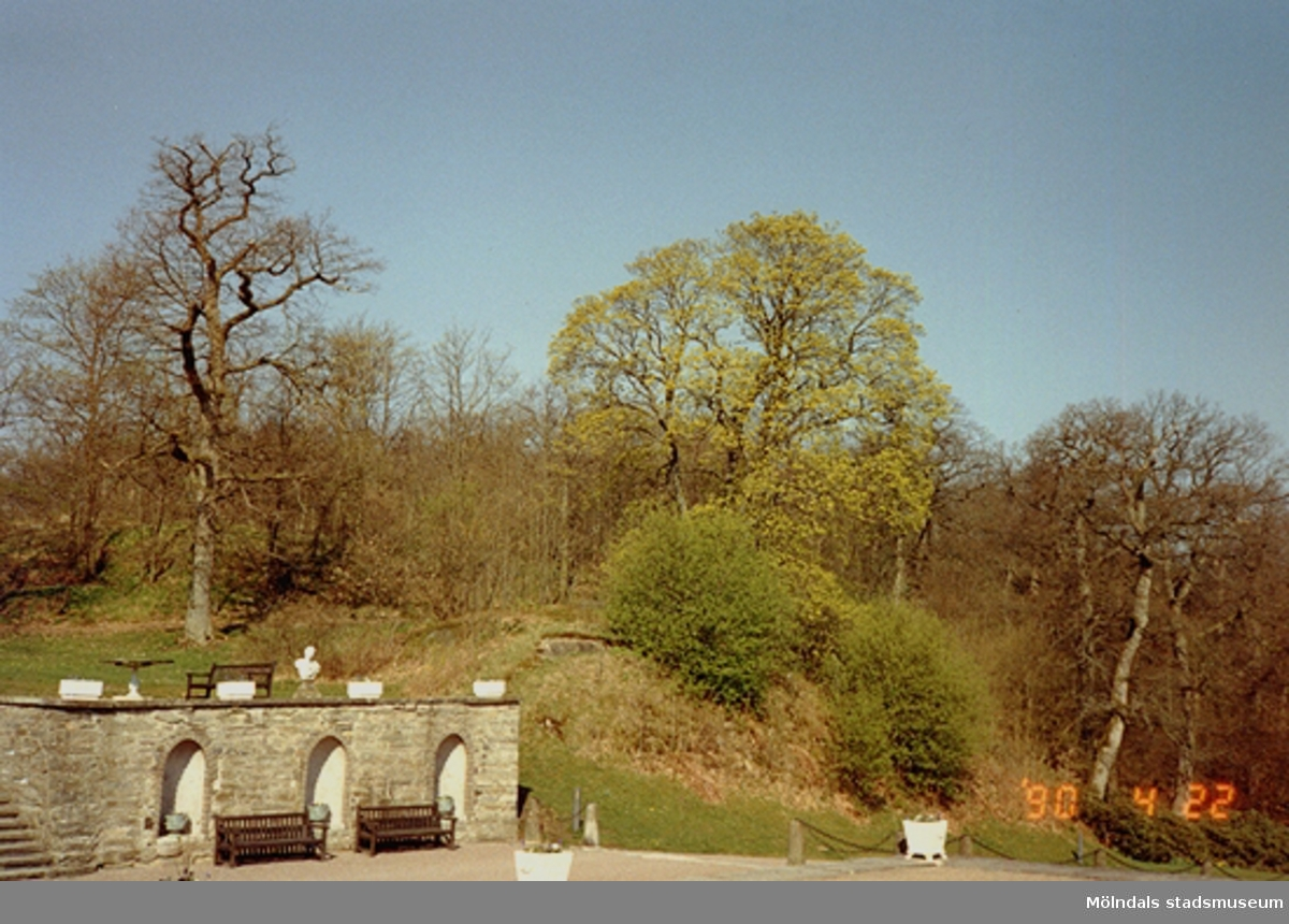 En stenmur med en kulle bakom. Gunnebo slott, april 1990.