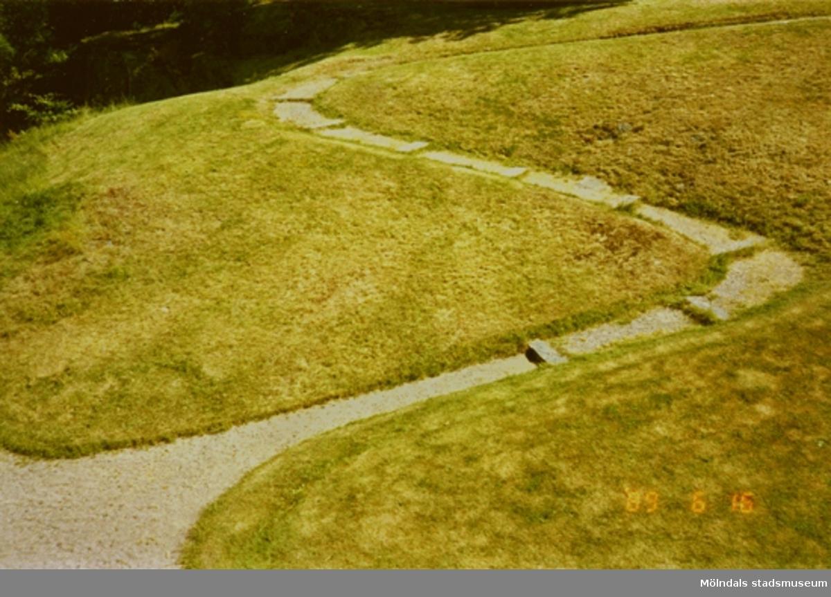 En stensatt trappa och grusgång, omgiven av gräsmattor.