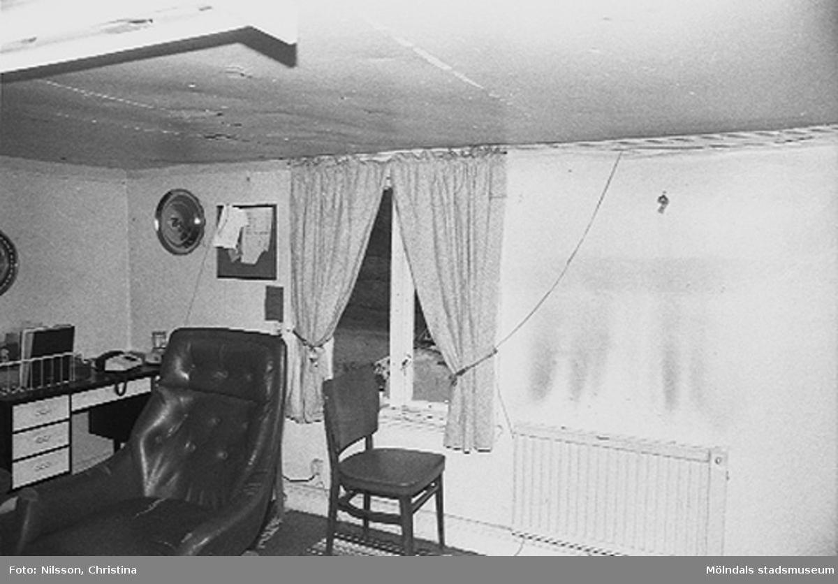 Interiör från ett rum. Övergången mellan vägg och tak är något välvd. Fönstret som vetter mot väster har hela glas och en mittpost. Innertaket är av masonit och i dåligt skick med hål på flera ställen.