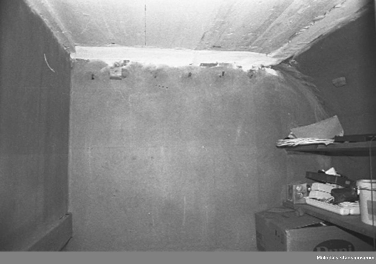 Interiör i fabriksbyggnad. Murvägg med hylla.