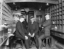 Till vänster Gustaf A. Roos, i mitten postexpeditör O.V. Eklund, sedermera postmästare i Årjäng. pkp 89. Foto omkring 1911-1913.