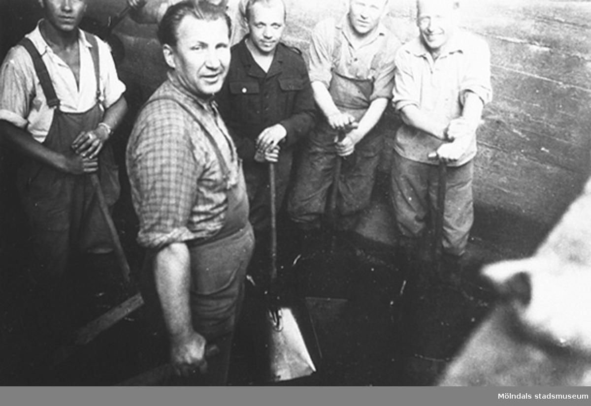 """Närbild från kanalrensningen utförd av män som i vanliga fall arbetade i färgeriet. Se föregående foto: 2002_0961.Hösten 1944 flydde 32.000 estländare från kriget i Estland till Sverige. Ett sextiotal personer tog jobb på August Werners textilfabrik i Lindome. Kvinnorna arbetade i spinneriet och männen i färgeriet.Mer information finns i uppsatsen """"Estländska textilarbetare i Lindome"""" som finns i Mölndals stadsmuseums interna arkiv."""