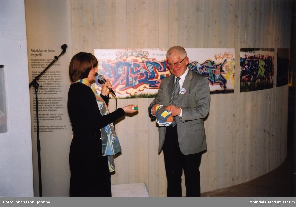 """Museichef Mari-Louise Olsson tillsammans med man i utställningen """"Alltså finns jag"""" på Mölndals museum, år 2003.  Utställningen """"Alltså finns jag"""" ...en utställning om graffitikultur på Mölndals Museum, Kvarnbygatan 12, Mölndal, pågick från 25 januari till 25 maj 2003. """"Alltså finns jag"""" var ett samarbete mellan Mölndals museum, Vitlycke museum, Bohusläns museum, Västergötlands museum och Konstkonsulenterna i Västra Götalandsregionen."""