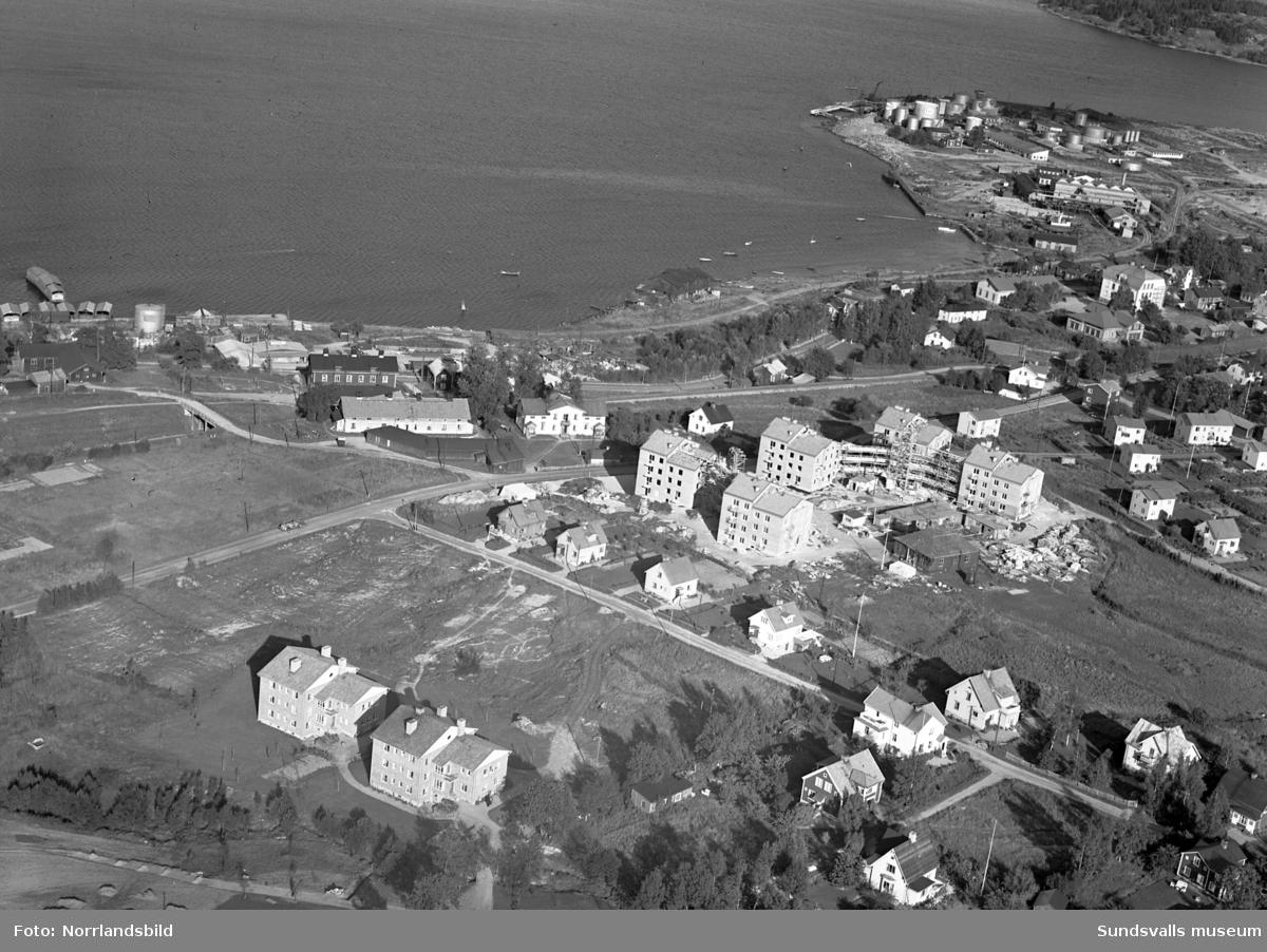 Flygfoto över Skönsmon och de nybyggda flerfamiljshusen femlingarna vid Björneborgsgatan. På bild nr 1 och 4 ses den mörka byggnaden med Mons salteri vid strandlinjen. Den gamla byggnaden mitt i bild intill flerfamiljshusen är rundradiostationen (ses även på bild 2, 3 och 4). Sundsvalls rundradio hade sin första utsändning den 1 mars 1925. Byggnaden användes till 1949 då den nya radiostationen i Ljusta, Skön, tillkom.