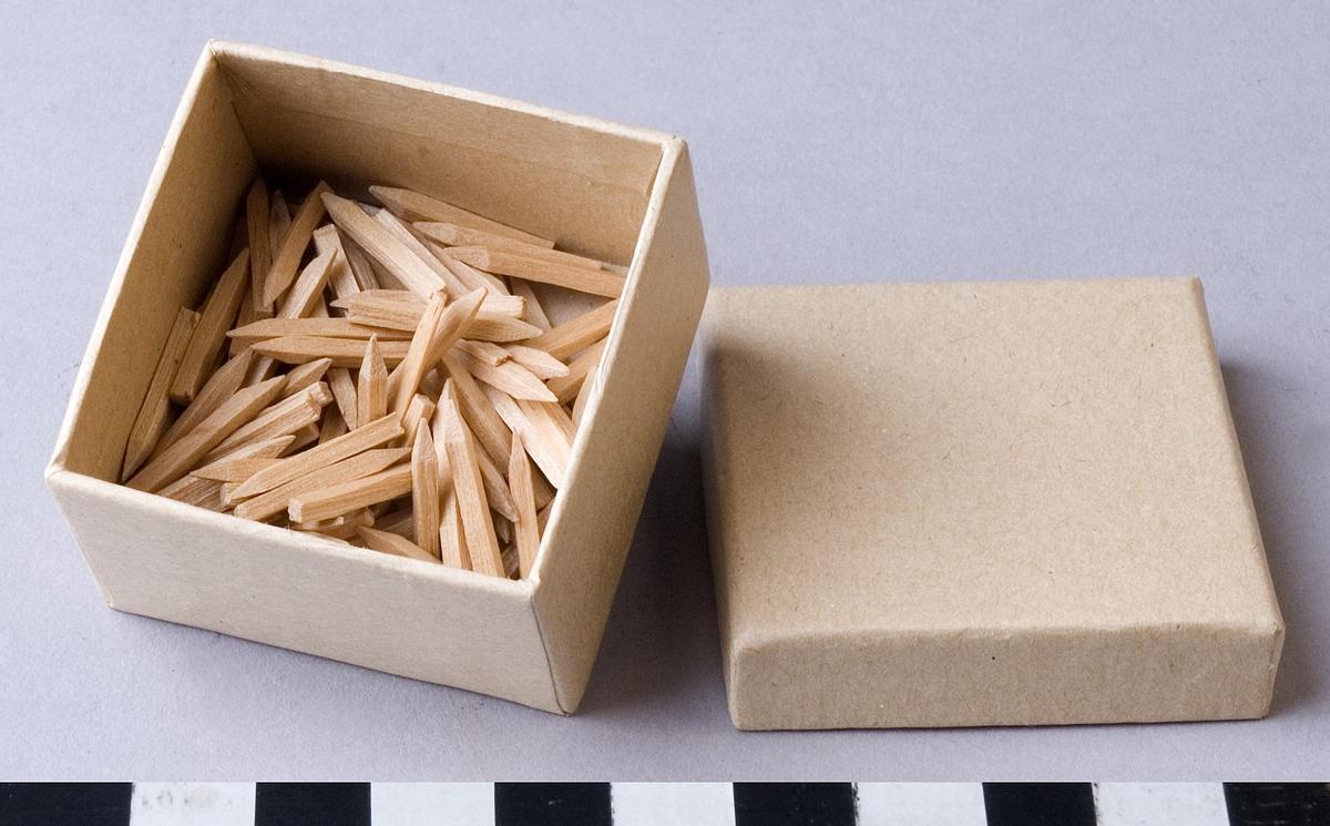 """Pligg, 120 stycken, av trä, 18 mm långa, fyrkantiga med en spetsig ände. Pligg stansas från så kallade  """"pliggband"""" av hyvlat trä. De används till att fästa klacken vid sulan. Först under 1840-talet började man i Sverige att använda pliggmetoden även vid sammanfogning av ovanläder och sula."""
