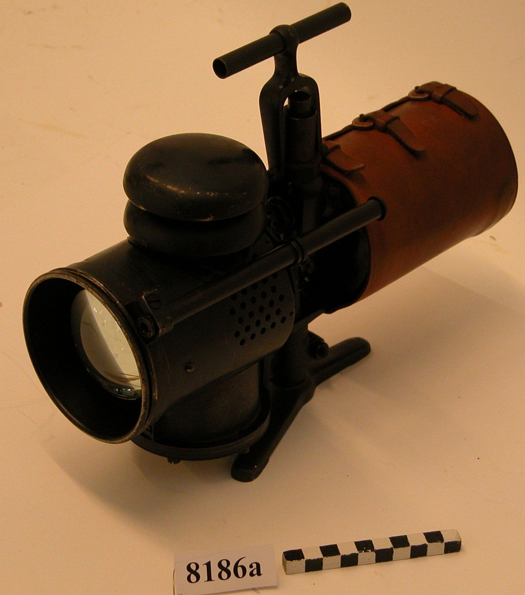 """För acetylengas. Lanterna av järnplåt, cylindrisk med en skjutbar mässingsfläns framför linsen, stativ och ett fällbart handtag av järn. Till lanternan är en acetylenbehållare ansluten. Ett läderhölje omsluter behållaren. Svartmålad. Mellan lanterna och behållare sitter på stativet en liten mätare med texterna """"Kg.pr.qcm"""", visare med skala 0-30, """"GASACCUMULATOR"""" och """"STOCKHOLM"""". På lampans högra sida en metallskylt med texten """"GASACCUMULATOR STOCKHOLM PATENT"""". På den nedersta flänsen på lampan är siffrorna 511 instansade. På lampans vänstra sida ett siktrör."""