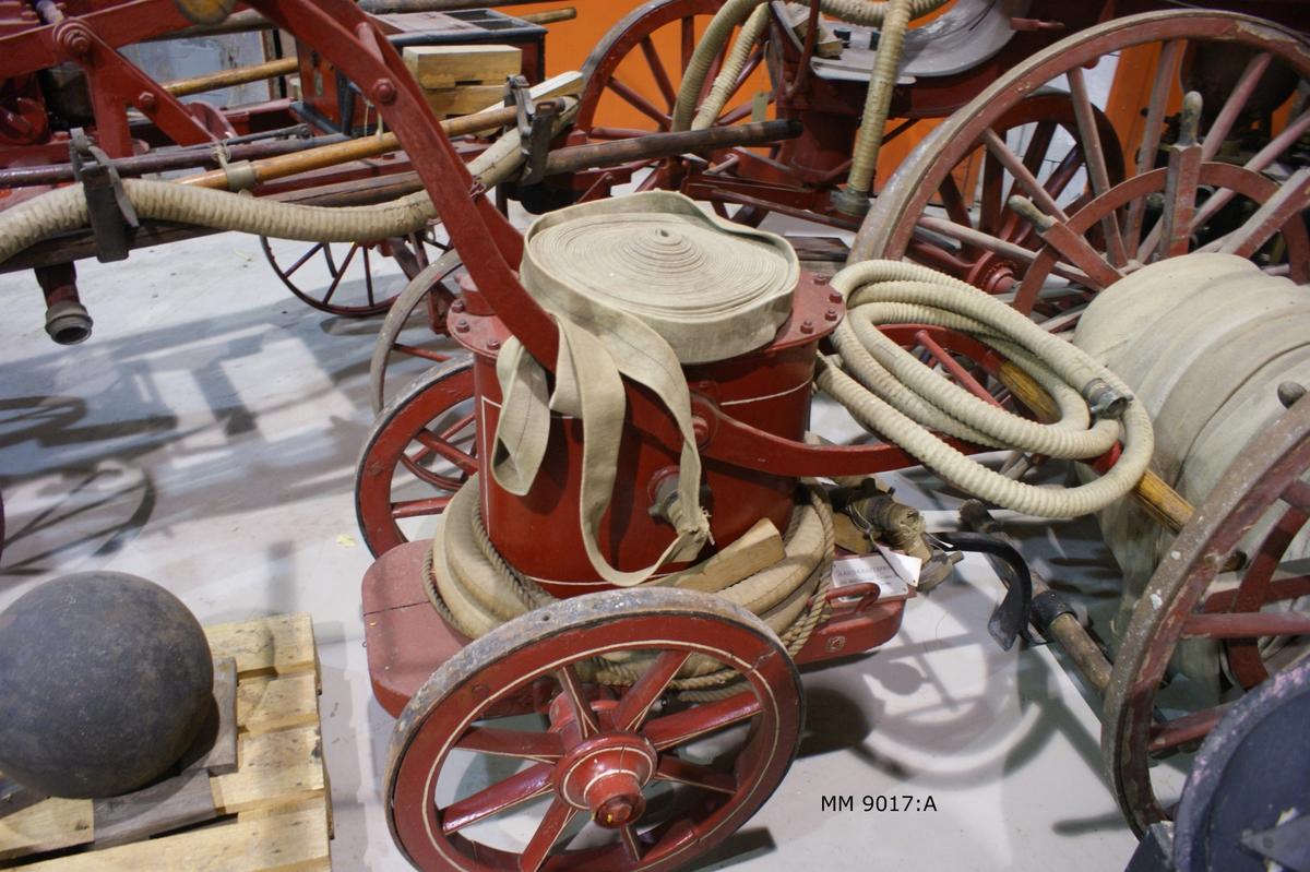 Brandspruta på tvåhjulig kärra för handkraft ( 6 man ). Av järnplåt och trä. Från mitten av 1800-talet.  Har från senare delen av 1800-talet tillhört Laboratorieholmen, Karlskrona. Sprutan ovalformad, rödmålad, med två pumparmar av järn, kopplad till sprutan. På hävarmarna tvärsgående trähandtag. Sprutan  fast till kärra, rödmålad, vars hjul är beslagna med ringar av järn, tjänstgörande som stöd, då sprutan är uppställd för pumpning. På vardera sidan av flaket en draglina.