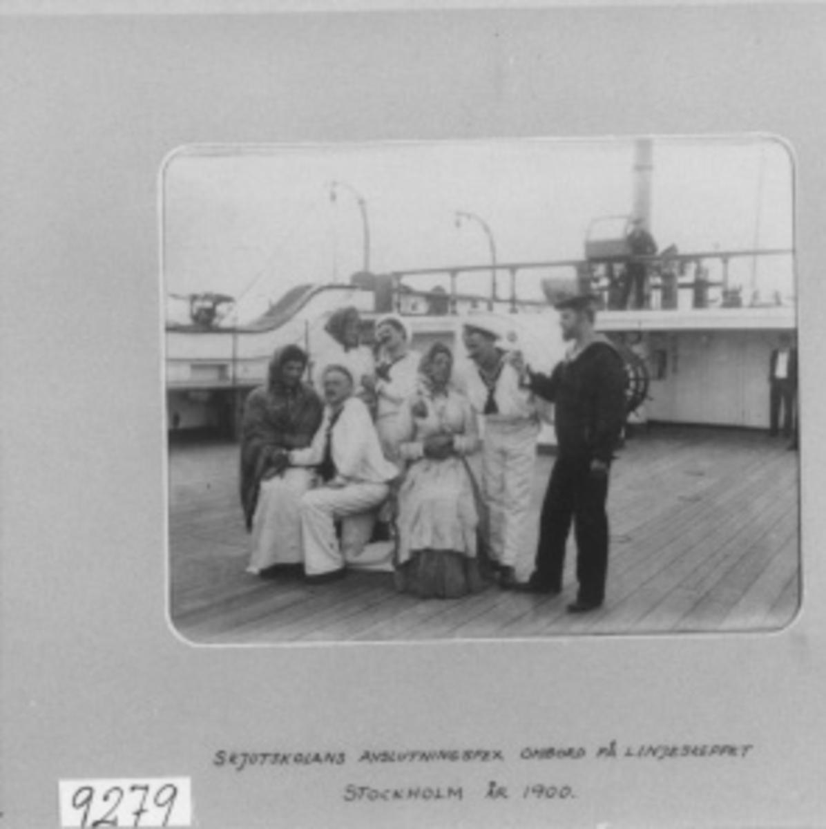 Fotografi med ram av ljusgrå papp. Märkt med bläck: Skjutskolan avslutningsspex ombord på linjeskeppet Stockholm 1900.