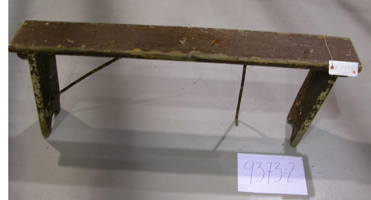Backlagsbänk av trä, brunmålad. Bänkens ben försedda med gångjärn för att kunna fällas in mot sittbrädans underkant. Vid användandet fästs benen till sittbrädan med järnhakar.