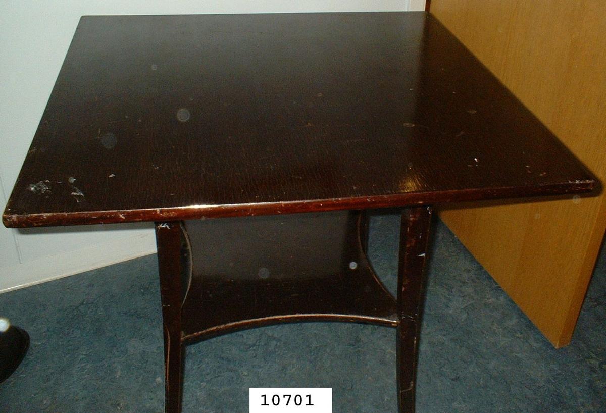 Spelbord av mahogny. Under bordsskivan en hylla, benen svängda.
