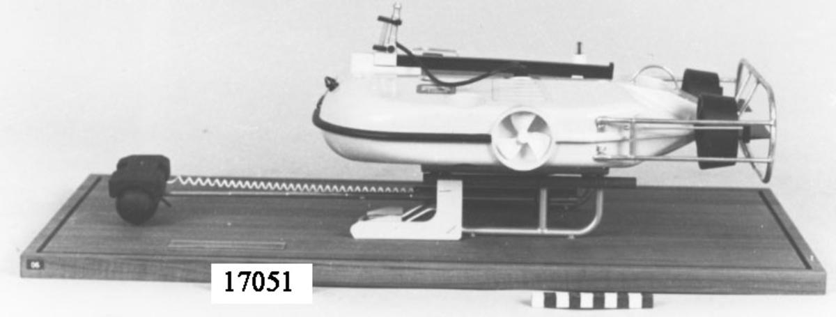 Modell av farkost: Dubbeluv monterad på träplatta med huv av plexiglas. Skrovet målat i gult. Försedd med åtta stycken propellrar: två i aktern med roder på dysorna, en stycken i vardera sida samt fyra stycken mindre i öppningar genom skrovet. I fören fällningsram som är utskjutbar och försedd med minförstöringsladdning ( MINFÖL ) samt ARM-kamera. Akter och köl skyddas av metallställningar. L= 400 mm B = 245 mm skala 1:5 (exklusive MINFÖL), monter: H = 240 mm  L = 680 mm  B = 330 mm