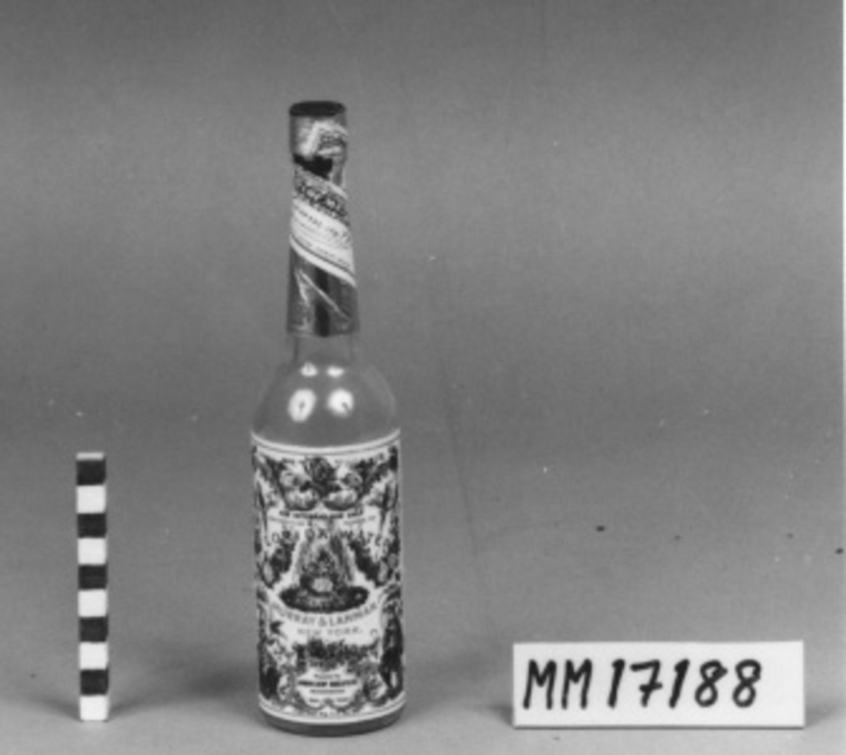 """Flaska av ofärgat glas med hög, smal hals och skruvkork. Flaskan är försedd med etikett på framsidan i polykromt tryck, föreställande en kvinna som håller i en fågel, och en man som spelar luta samt fåglar, blommor och rocaille ornament. Tryck. """"FLORIDA WATER MURRAY & LANMAN NEW YORK"""" samt """"FOR EXTERNAL USE ONLY CONTENTS 7_ 02. FL. ALCOHOL75%"""" med mera. Flaskans hals är omsluten av silverfärgat papper med firmanamn i svart på vit botten. Korken är av svart plast. Flaskan är tömd på sitt innehåll. Anmärkning: Utrikespinal"""