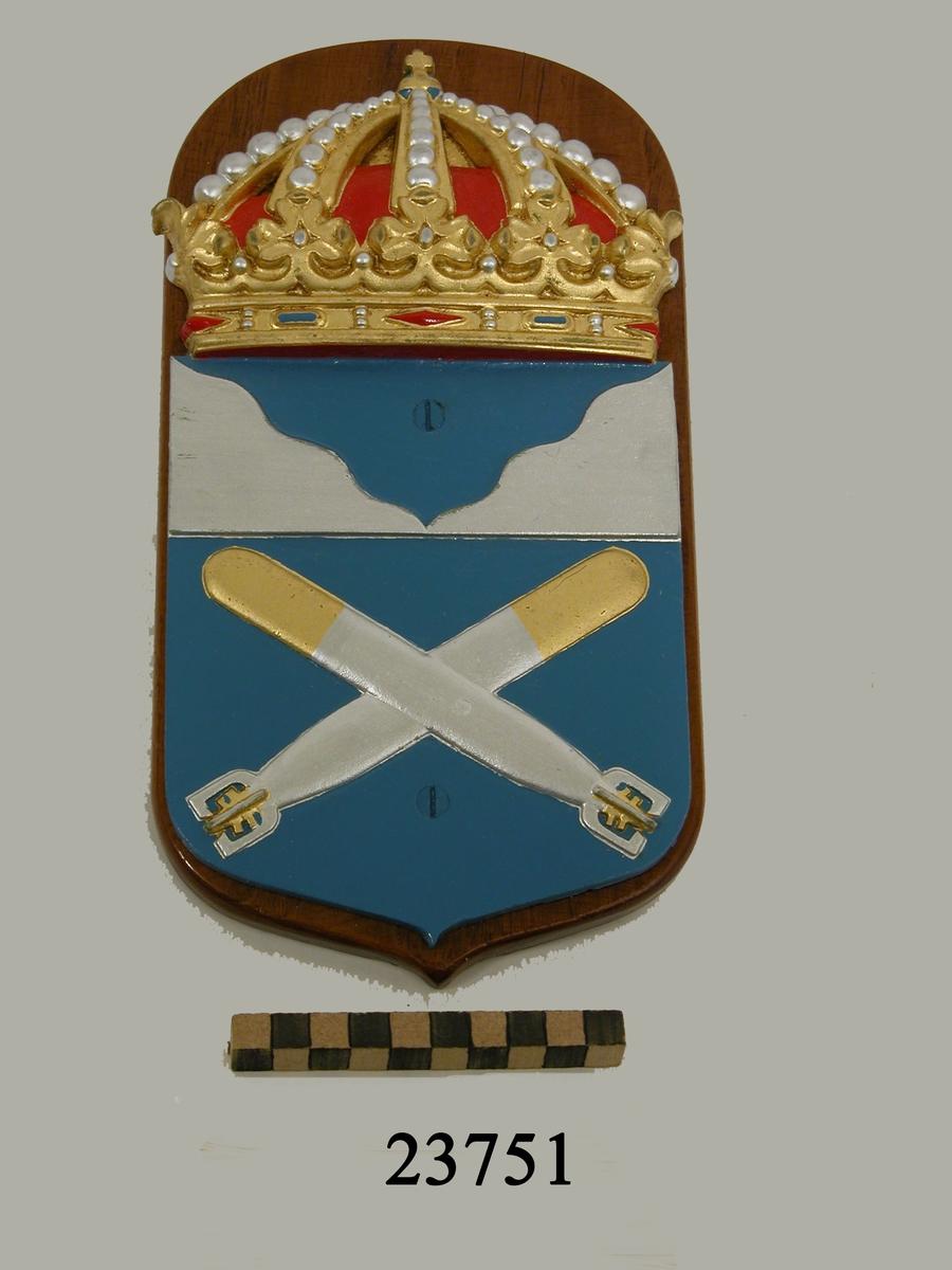 Krönt vapensköld av gjuten plast monterad på fernissad platta av trä. Emblemet består av blåfärgad sköld som är delad i två fält. I det övre fältet, silverfärgad kustkontur. I det nedre två korslagda torpeder, silverfärgade, spetsarna i guld. På baksidan skrivet T48.
